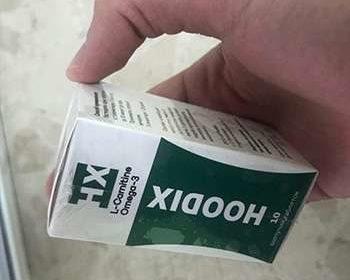 Упаковка hoodix для похудения в руках у мужчины